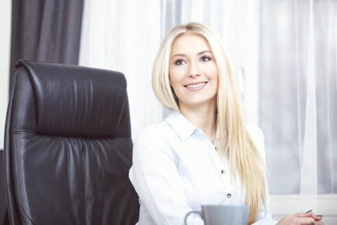 Portrait of smiling blond woman sitting in her office - SEGF000484