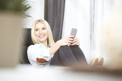 Portrait of smiling blond woman sitting at desk with her smartphone - SEGF000493