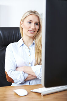 Portrait of smiling blond woman sitting at desk looking at computer - SEGF000499