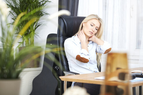 Portrait of overstressed blond woman sitting at her desk - SEGF000505