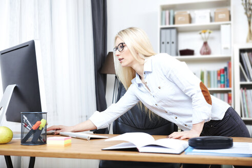 Young woman watching something at computer in her home office - SEGF000508