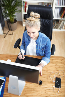 Blond woman sitting at desk working with graphics tablet - SEGF000520