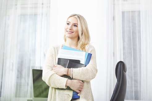 Portrait of smiling blond woman holding documents - SEGF000529