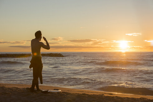 Back view of surfer standing on the beach watching sunrise - SKCF000084