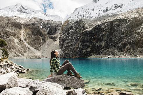 Peru, Huaraz, Huascaran National Park, woman relaxing after a trekking on lagoon, Laguna 69 - GEMF000824