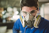 Portrait of a construction worker wearing a protective mask - RAEF000990