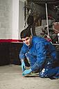 Bricklayer removing irregularities on floor screed with spatula - RAEF000996