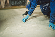 Bricklayer marking irregularities on floor screed - RAEF001002