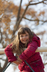 Portrait of smiling little girl climbing on playground equipment - XCF000073