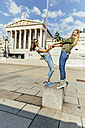 Austria, Vienna, two young women having fun in front of the parliament building - AIF000299