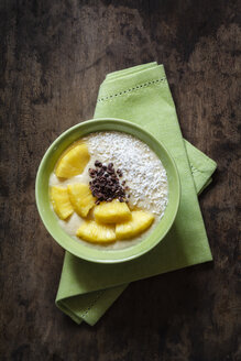 Bowl of fruit smoothie garnished with pineapple slices, coconut flakes and chocolate shaving - EVGF002912