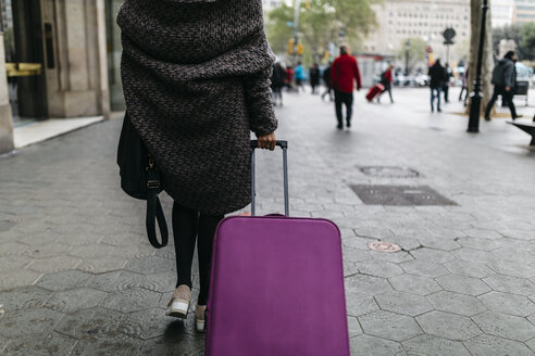 Spain, Barcelona, young woman with suitcase walking in the city - JRFF000512