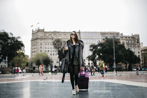 Spain, Barcelona, young woman with suitcase walking on Placa Catalunya - JRFF000515