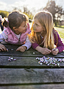 Two little girls lying on a boardwalk looking at each other - MGOF001717