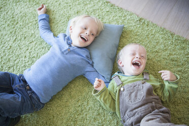 two laughing little brothers lying on green carpet at home - RBF004245