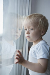 Portrait of little blond boy looking through window - RBF004254