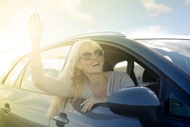 Happy woman in car waving - MFRF000599