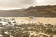 Spain, Fuerteventura, Jandia, woman on rocky beach - MFRF000608