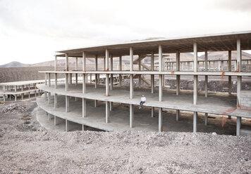 Spain, Fuerteventura, Jandia, architect sitting in building shell - MFRF000611