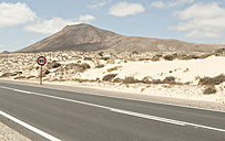 Spain, Fuerteventura, Corralejo, Parque Natural de Corralejo, view of empty road and road sign - MFRF000617
