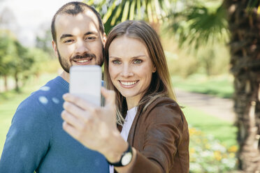 Happy couple taking selfie with smartphone in a botanical garden - MFF002963