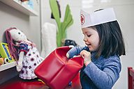 Little girl searching medical toys inside of a red bag - DAPF000080