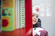 Little girl with nurse cap and doll looking from behind a bookshelf - DAPF000086
