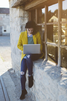 Woman using laptop outside building - JPF000122