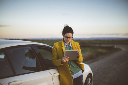 Woman using digital tablet at car - JPF000125