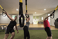 Group of young people training on elastic cord in gym - JASF000624