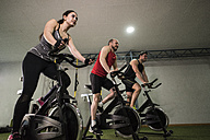 Group of young people training on exercise bike in gym - JASF000627
