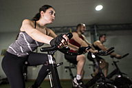 Group of young people training on exercise bike in gym - JASF000630