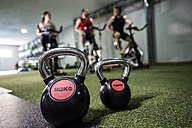 Group of young people training on exercise bike in gym with kettlebells in foreground - JASF000651