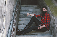 Portrait of serious looking man with cigarette sitting on stairs - RTBF000102