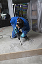 Worker treating the cement floor with a jackhammer - RAEF001031