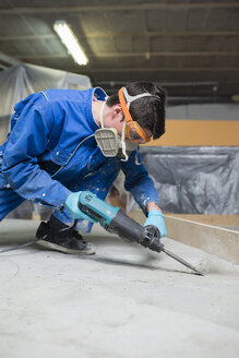 Worker treating the cement floor with a jackhammer - RAEF001034