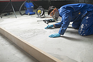 Worker checking the level of the concrete floor - RAEF001037