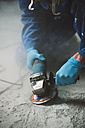 Worker smoothening cement floor with an angle grinder - RAEF001040