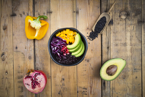 Lunch bowl with black rice, avocado, yellow bell pepper, red cabbage and pomegranate seed on wood - LVF004726