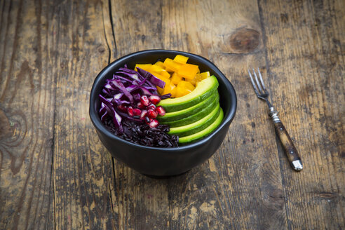 Lunch bowl with black rice, avocado, yellow bell pepper, red cabbage and pomegranate seed on wood - LVF004729