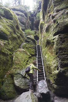 Germany, Saxony, Saxon Switzerland National Park, Female hiker between sandstone rock, ladder - BSCF000527