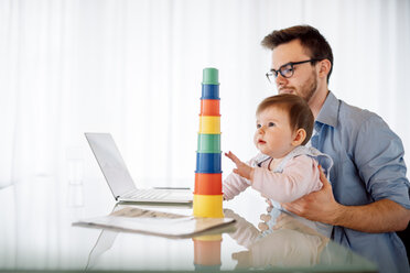 Young man with baby girl on his lap sitting at desk - BRF001300