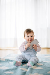 Portrait of smiling baby girl sitting on blanket holding smartphone - BRF001303