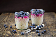 Two glasses of overnight oats with blueberries and berry juice on wood - LVF004736