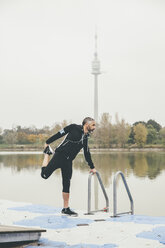 Austria, Vienna, jogger doing stretching exercise on Danube Island - AIF000311
