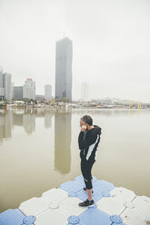 Austria, Vienna, jogger doing stretching exercise on Danube Island - AIF000314