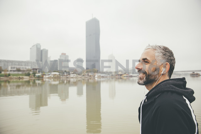 Austria, Vienna, portrait of smiling jogger with earphones in front of Donau City - AIF000317 - AustrianImages/Westend61