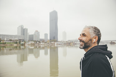Austria, Vienna, portrait of smiling jogger with earphones in front of Donau City - AIF000317