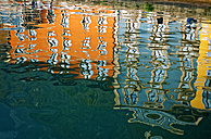 Italy, Lake Garda, Limone sul Garda, water reflections of colourful facades in harbour basin - LHF000492
