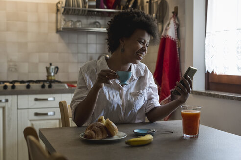 Laughing young woman with espresso cup sitting in her kitchen looking at phablet - MAUF000425